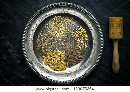 Set of gyros spices on a tin plate and pestle horizontal