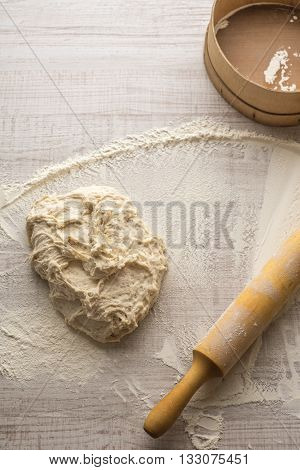 Crumble flour rolling pin dough and a sieve on the table vertical