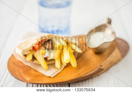 Gyros dzatziki in a gravy boat on a wooden stand horizontal