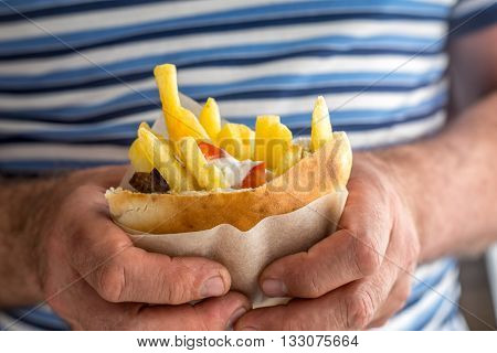 Gyros with french fries in a napkin in the hands of a man on striped background horizontal