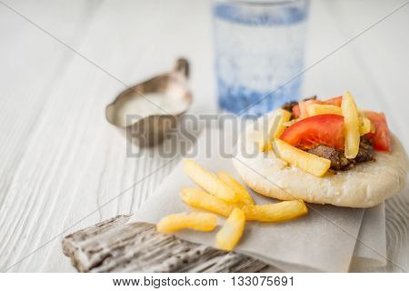 Gyros with fried potatoes meat tomato on pita bread stand and glass of water horizontal