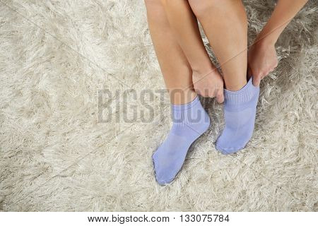 Woman putting on socks, top view