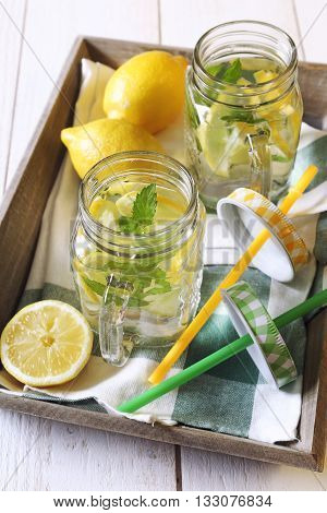 Cool refreshing drink: pure water lemon and mint on a wooden tray