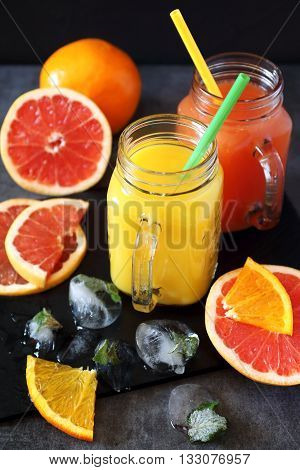 Grapefruit and orange juice in two glass jug and fruits