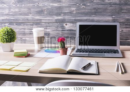 Closeup of modern office desktop with blank laptop notepad plants coffee cup and other items on wooden background. Mock up
