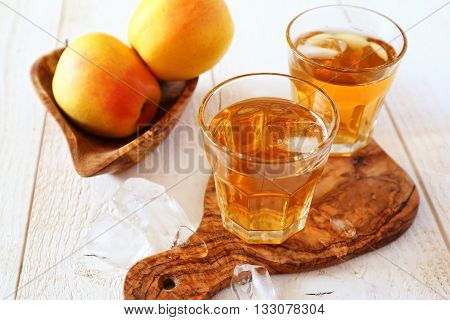 Apple juice in two glass and two Golden apples