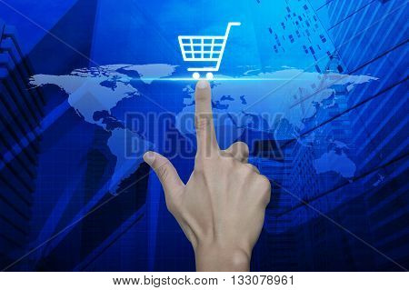 Hand pressing shopping cart icon over map and city tower Shopping online concept Elements of this image furnished by NASA