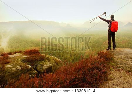 Alone Adult Backpacker With Poles In The Air,  Open View On Mountain Valley, Misty Rainy Day