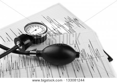 Medical manometer lying on cardiogram chart close up