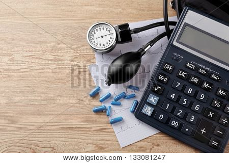 Medical manometer, pills and cardiogram on wooden background