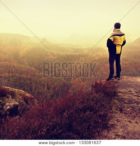 Rear View Of Male Hiker In Yellow Black Jacket On Rocky Peak While Enjoying A Daybreak After Rainy N