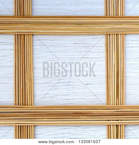 Frame from thin bamboo sticks on white wooden background