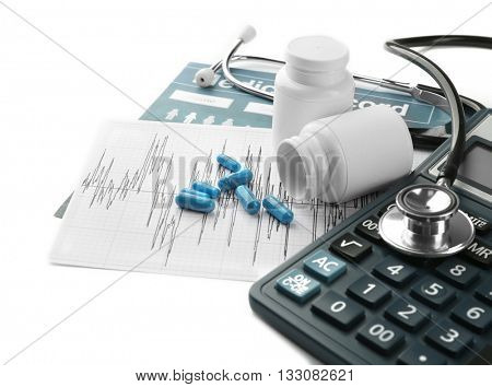 Medical concept. Medical record with pills,  calculator, and a stethoscope on white background