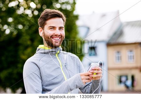 Young hipster runner in town with smartphone and earphones, listening music