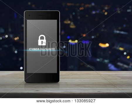Key icon and cyber security text on modern smart phone screen on wooden table in front of blurred light city tower Cyber security concept