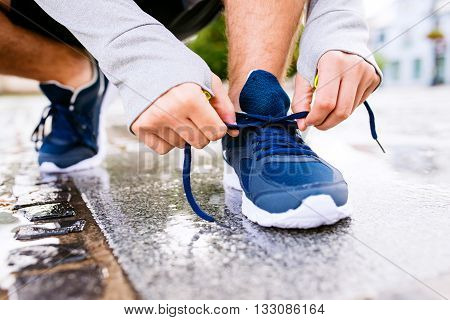 Close up of legs of unrecognizable man running in the town, puddle