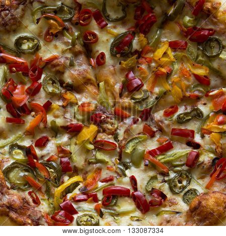 A Pizza topped with Bell Peppers and Jalapeños