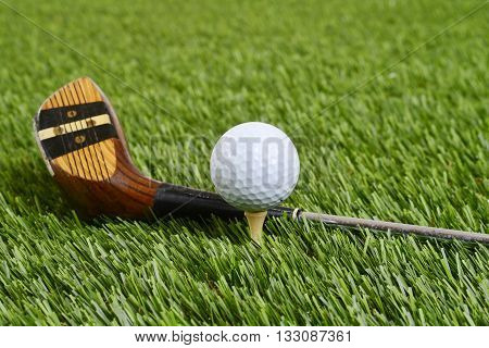 golf ball with driver club on grass