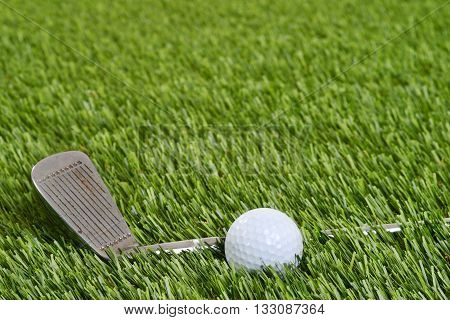 golf wedge club with ball on grass