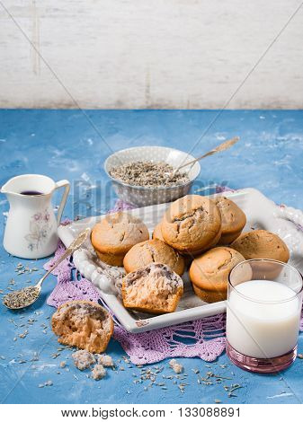 Lavender muffins with ingredients - lavender syrup, milk and lavender flowers on blue textured background. Vertical image