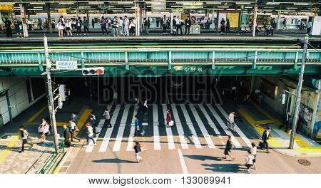 Tokyo - May 2016: Street view with train platform, crosswalk and people at Nakano Station.