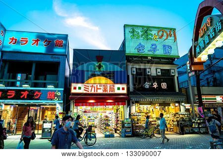 Tokyo - May 2016: Evening street view of Koenji with people and glowing neon lights.