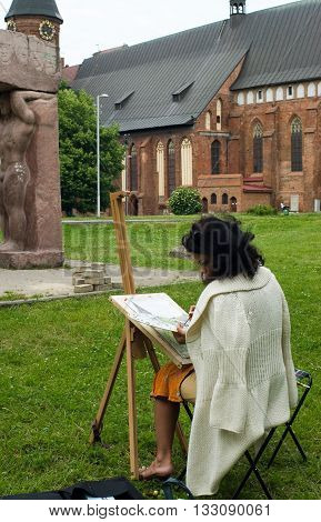 Kaliningrad, Russia - June 21, 2010: Artist creates on open-air near Epokha Vozrozhdeniya sculptural group. Kant island