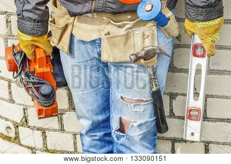 Construction worker with electro saw and spirit level near wall