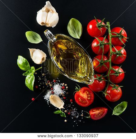 Top view of olive oil in a glass sauceboat cherry tomatoes a mixture of peppers basil garlic and salt on a black background.
