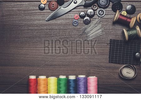 buttons, needles and multicolored threads on wooden table