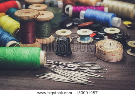 needles buttons and threads on brown wooden table
