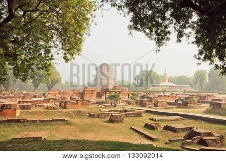 Green park with ruined temple walls and sacred Dhamekh Stupa in Sarnath. Indian landmark place where Gautama Buddha first taught the Dharma at 500 BC.