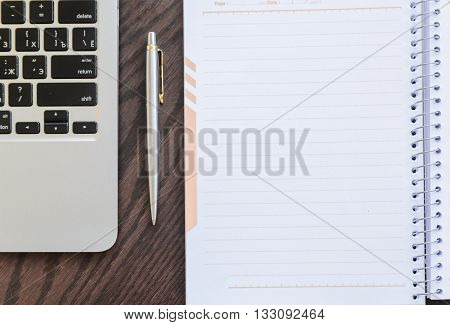 Notepad, pen and laptop on old brown wooden desk.