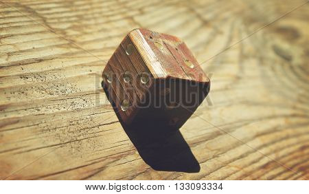 Old wooden dice on a wooden background