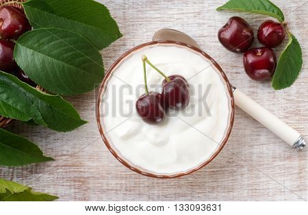Overhead view of natural greek yoghurt with summer fruit and green leaves in a glass bowl on a wooden table room for text