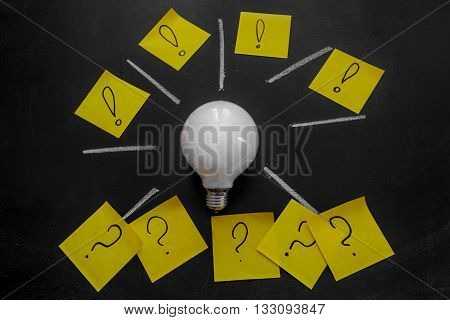 Light bulb and exclamation marks and question marks written on the yellow stickers on the black chalkboard light bulb idea business idea business concept Innovation concept
