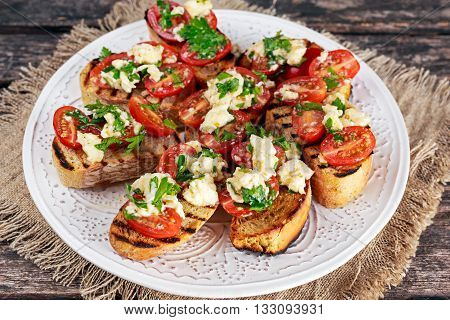 Two-bite grilled appetizer bruschettas with red grape tomatoes, mozzarella and parsley sprinkle.