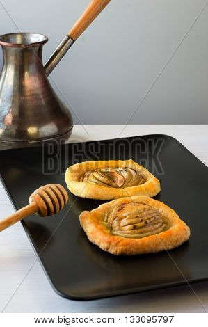 Tasty puff pastry with apple shaped roses on plate on table