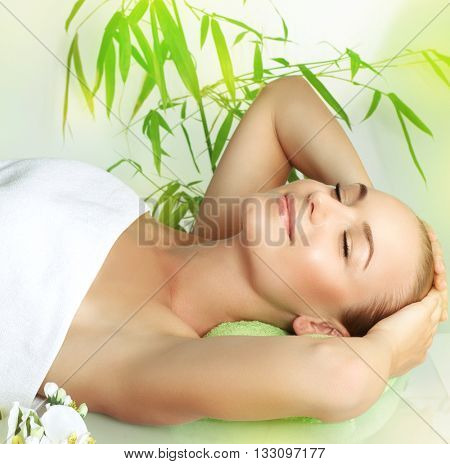 Happy smiling girl with closed eyes lying down on massage table in a spa salon, beauty treatment, pampering and skin care