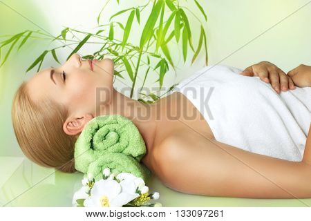 Beautiful calm woman with closed eyes lying down on the massage table and enjoying spa procedures, alternative medicine, healthy lifestyle