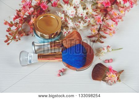 There White and Pink  Branches of Chestnut Tree,Bronze Powder with Mirror and Make Up Brown and Blue Brushes with Cream  are on White Table,Top View