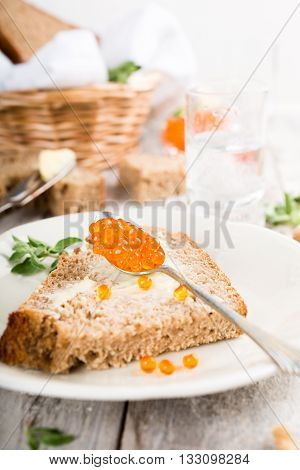 Open sandwich with red caviar and butter, bowl red caviar and fresh baked homemade healthy bread on old white wooden table background. Healthy food.