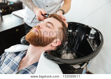 Man washing head to client in barbershop