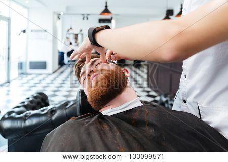 Barber shaving man with straight razor in barbershop