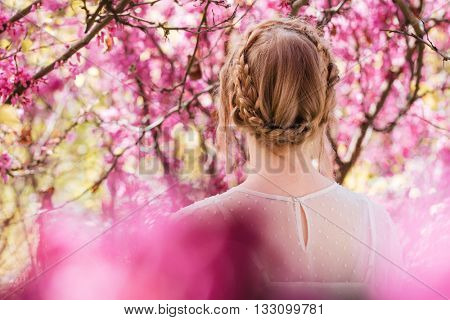 Back view of blonde young woman standing in spring blooming garden