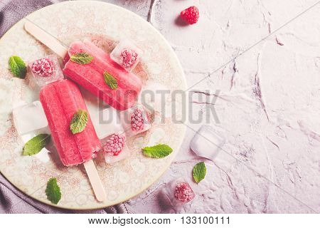 Homemade raspberry popsicles on plate with ice and berries. Summer food concept with copy space for text. Top view. Retro style toned.
