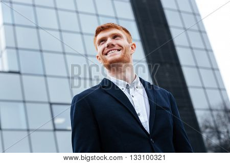 Smiling businessman looking away outdoors with glass building on background