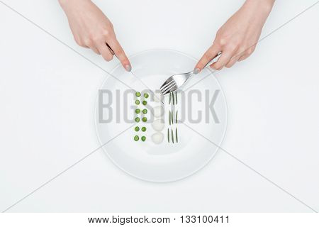 Top view of hands of young woman eating green peas, mozzarella and herbs using fork and knife over white background