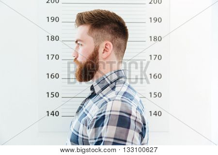 Side view portrait of arested man standing on measure wall