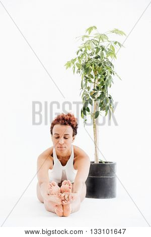 Peaceful african american young woman sitting near the tree in pot and doing yoga exercises over white background